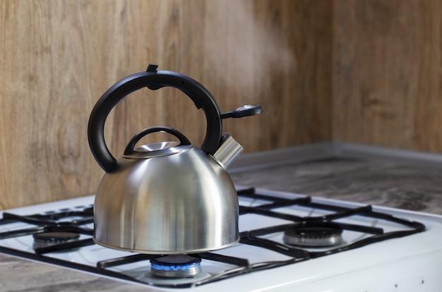 Metalen zilveren moderne waterkoker op gasfornuis in de keuken