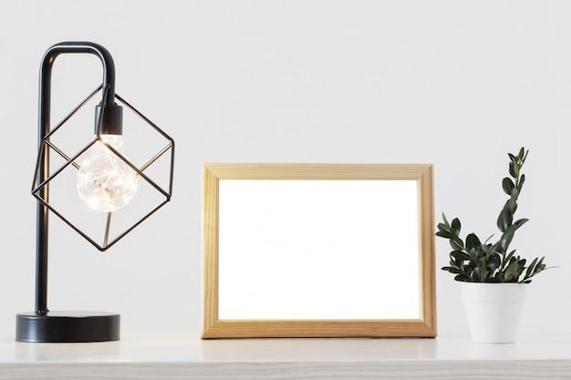 Metalen zwarte lamp, houten frame en plant in wit interieur