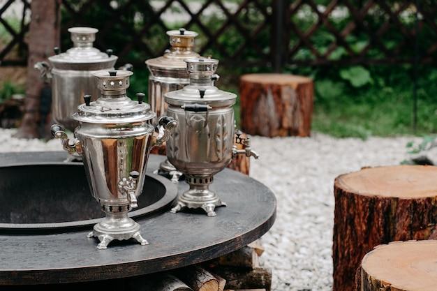 Metalic samovars buiten en houten stronken rondom