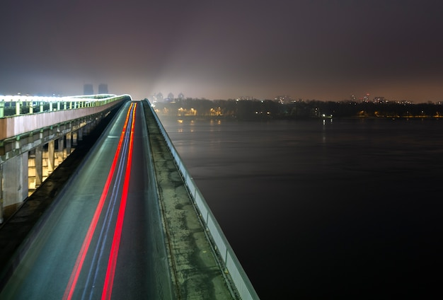 Metro brug over de rivier de dnjepr in kiev 's nachts licht parcours op de brug' s nachts