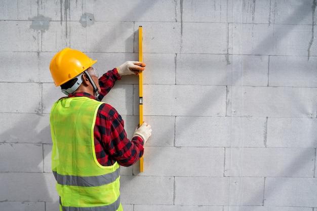Metselaar bouwer met behulp van het waterpeil, controleer de helling van geautoclaveerde cellenbetonblokken. muren, stenen plaatsen op de bouwplaats