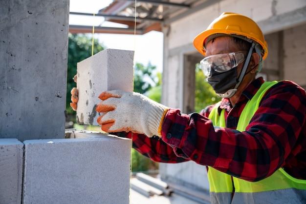 Metselaar bouwer werken met geautoclaveerd cellenbetonblokken. muren, stenen plaatsen op de bouwplaats