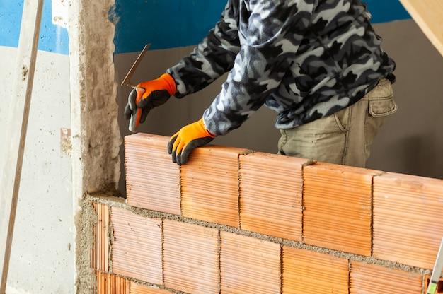 Metselaar die baksteenmetselwerk op binnenlandse muur installeert.