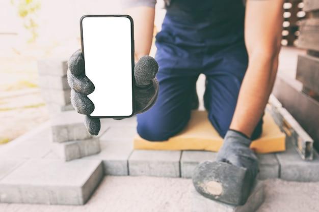 Metselaar die de telefoon met het lege scherm in de hand op handschoenen houdt. mockup voor huisreparatie of -bouw
