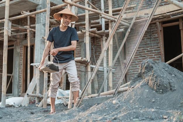 Metselaar die schop houdt terwijl hij zand met woningbouwachtergrond draagt