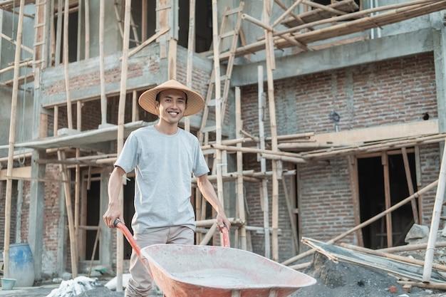 Metselaar die terwijl het duwen kruiwagen met woningbouwachtergrond loopt