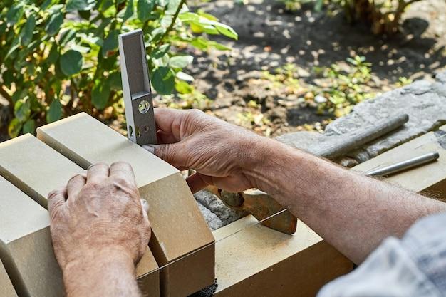 Metselaar egaliseerstenen op het nieuwe hek van gevelstenen met behulp van bouwniveau