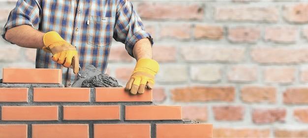 Metselaar industriële arbeider die baksteenmetselwerk installeert