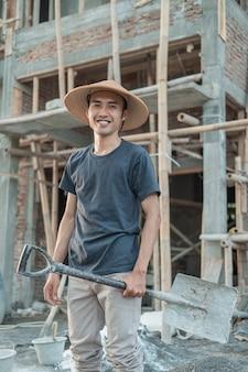 Metselaar met een glimlachende hoed staat op met een schop naar de onafgemaakte constructie van het huis