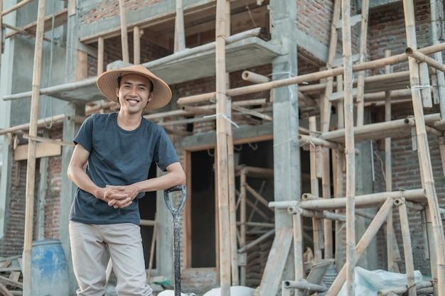 Metselaar met een glimlachende hoed terwijl hij met een schop naar de onafgemaakte constructie van een huis staat