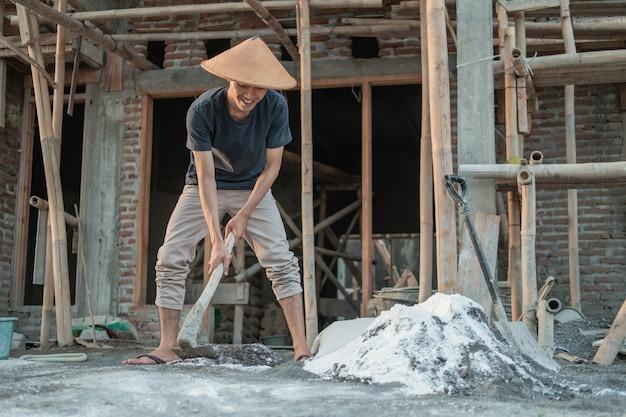 Metselaar met een schoffel voor zand en cement voor gebouwen tegen de achtergrond van het bouwen van huizen