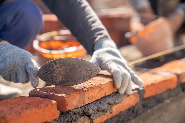 Metselaararbeiderarbeider die baksteenmetselwerk met het mes van de troffelstopverf installeren bij bouwwerf