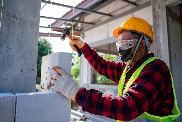 Metselaarbouwer gebruikt een hamer om te helpen met geautoclaveerde cellenbetonblokken. muren, stenen plaatsen op de bouwplaats
