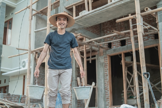 Metselaars dragen lachende hoeden terwijl ze emmers naar hun werk dragen