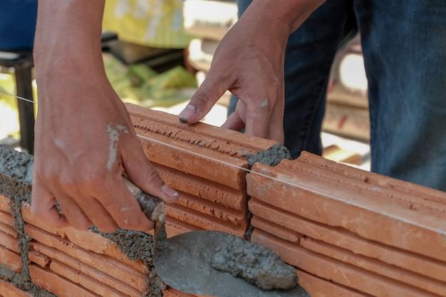 Metselaarwerknemer die baksteenmetselwerk op buitenmuur installeert.