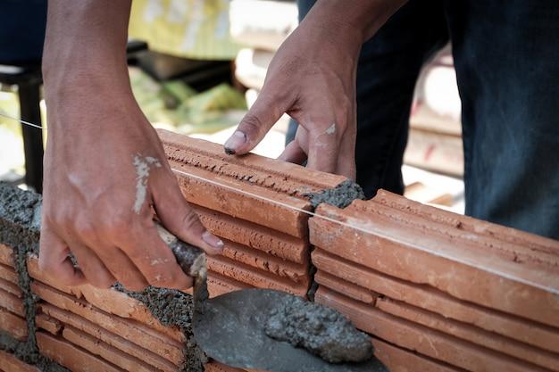 Metselaarwerknemer die baksteenmetselwerk op buitenmuur installeren.