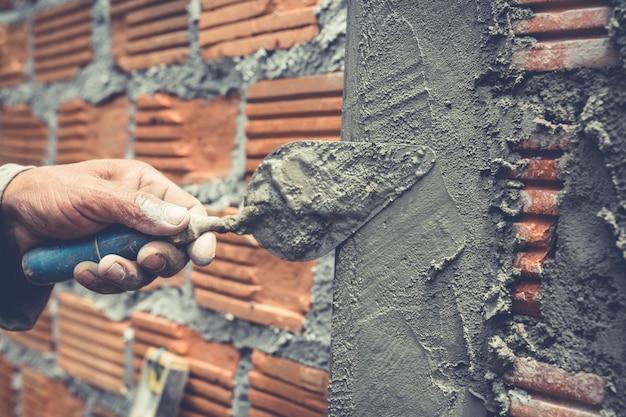 Metselen. bouwvakker die een bakstenen muur bouwt.