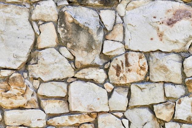 Metselwerk rotswand textuur. stenen in fundering van oud kasteel. stenen muur achtergrond voor ontwerp of illustratie
