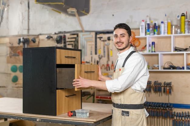 Meubelfabriek, kleine bedrijven en mensenconcept - jonge man aan het werk bij de meubelproductie.