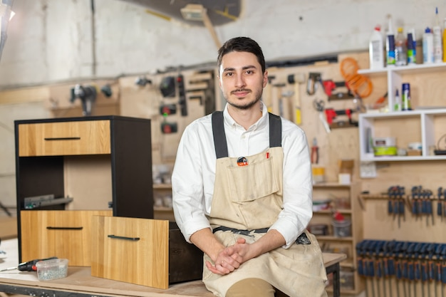 Meubelfabriek, kleine bedrijven en mensenconcept - portret van een glimlachende mannelijke werknemer bij