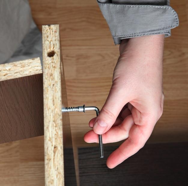 Meubelmontage, bevestiging houtschroef wordt in spaanplaatpanelen geschroefd.