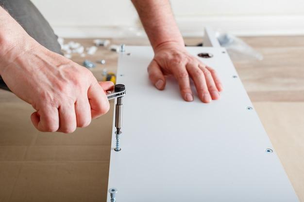 Meubelmontage mannelijke handen meester verzamelt meubels met behulp van schroevendraaier gereedschap instrument thuis m...