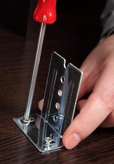 Meubelmontage, montagebeugels schuifrails met een handschroevendraaier.