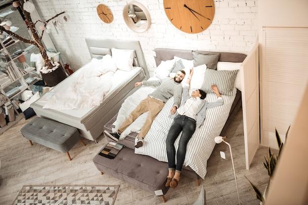 Meubels voor slaapkamer. geïnteresseerd paar dat de kwaliteit van de matras voor hun toekomstige leven samen onderzoekt terwijl ze in de showroom liggen
