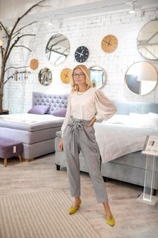Meubelsalon, bedden. vrouw in grijze broeken en gele schoenen die zich dichtbij nieuwe bedden in een meubilairopslag bevinden, hand op de riem, kalm.
