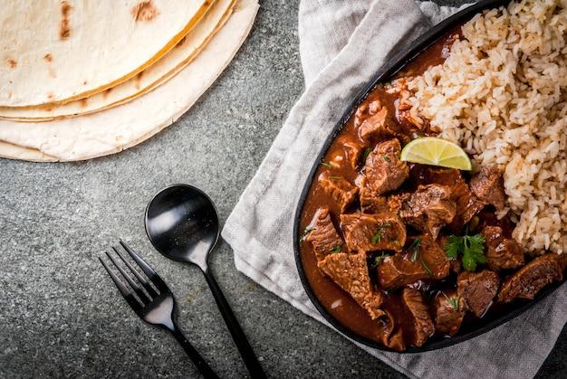 Mexicaans en amerikaans traditioneel voedsel hutspotrundvlees met tomatenkruidenpeper - chili colorado met gekookte rijstkalktortilla's