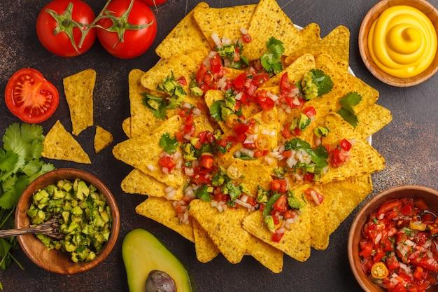 Mexicaans eten concept. nachos - gele mais totoposchips met verschillende sauzen in houten kommen: guacamole, kaassaus, pico del gallo, bovenaanzicht