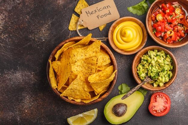 Mexicaans eten concept. nachos - gele mais totoposchips met verschillende sauzen in houten kommen: guacamole, kaassaus, pico del gallo, kopie ruimte, bovenaanzicht