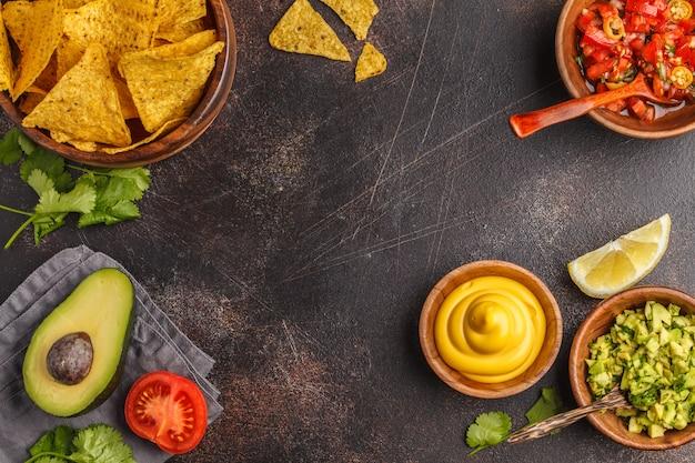Mexicaans eten concept. nachos - gele maisentoposchips met diverse sauzen in houten kommen: guacamole, kaassaus, pico del gallo, frame van eten, bovenaanzicht, kopie ruimte.