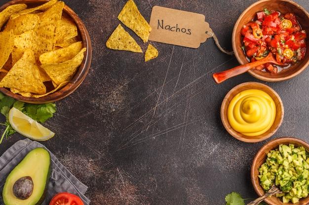 Mexicaans eten concept. nachos - gele maisotoposchips met diverse sausen in houten kommen: guacamole, kaassaus en tomatensaus, frame van voedsel, bovenaanzicht, exemplaarruimte.