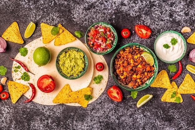 Mexicaans eten concept: tortilla's, nacho's met guacamole, salsa, chili con carne, bovenaanzicht.