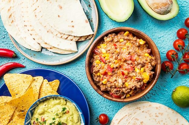 Mexicaans eten mix nacho's, fajitas, tortilla, guacamole en salsa sauzen en ingrediënten over blauw oppervlak. bovenaanzicht