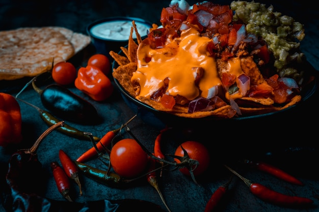 Mexicaans eten nacho's kom op donkere pico de gallo kaas en peper in voedselstijl