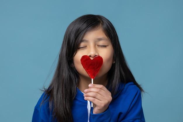 Mexicaans latijns meisje dat een hartvormig concept van de lolly zelfliefde kust