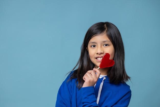 Mexicaans latijns meisje dat hartvormige lolly zelfliefde concept houdt
