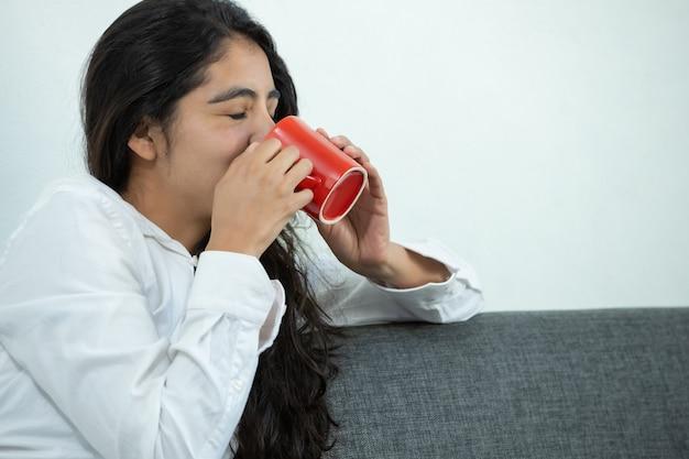 Mexicaans meisje dat koffie op rode mok drinkt