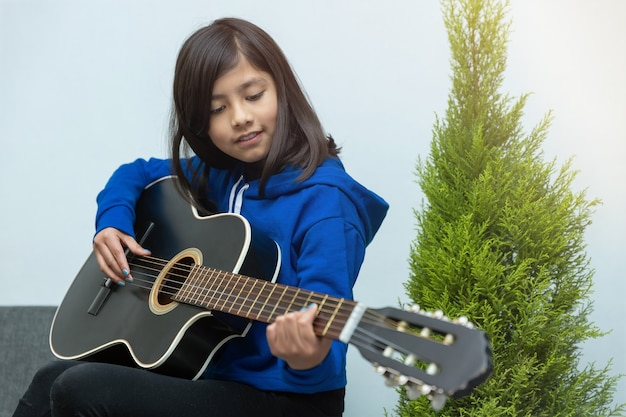 Mexicaans meisje dat thuis gitaarlessen volgt vanwege het coronavirus, thuisonderwijs