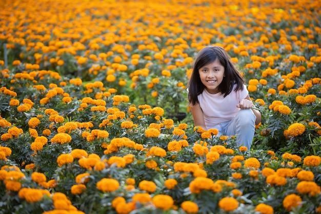 Mexicaans meisje kijken en glimlachen naar cempasuchil bloemen op het veld