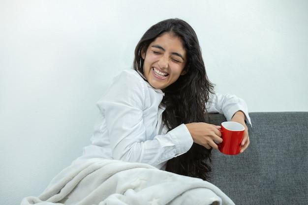 Mexicaans meisje koffie drinken op rode mok lachen