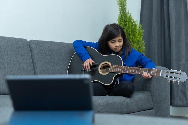 Mexicaans meisje nam thuis gitaarlessen gefrustreerd vanwege het afsluiten van het coronavirus, thuisonderwijs