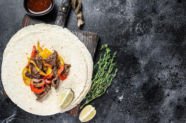 Mexicaanse fajita's met gekleurde peper en uien, geserveerd met tortilla's en salsa. zwarte achtergrond. bovenaanzicht. kopieer ruimte.