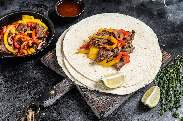 Mexicaanse fajita's met gekleurde peper en uien, geserveerd met tortilla's en salsa. zwarte achtergrond. bovenaanzicht.