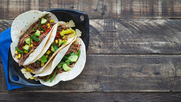 Mexicaanse fajitas in zwarte lade op houten planken. kopieer ruimte. mexicaans eten concept.
