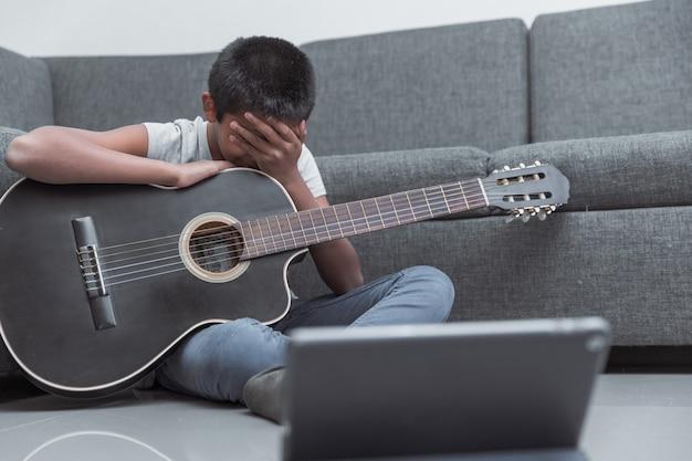 Mexicaanse gefrustreerde jongen die thuis gitaarlessen volgt vanwege het coronavirus, thuisonderwijs