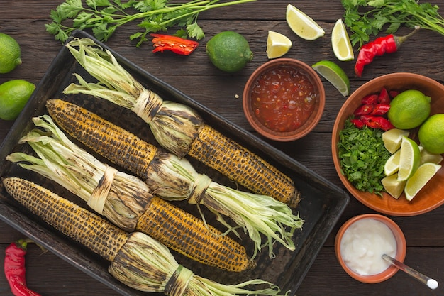 Mexicaanse gegrilde maïs met hete chilisaus op de eettafel, bovenaanzicht