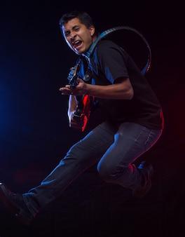 Mexicaanse gitarist die op zwarte oppervlakte springt